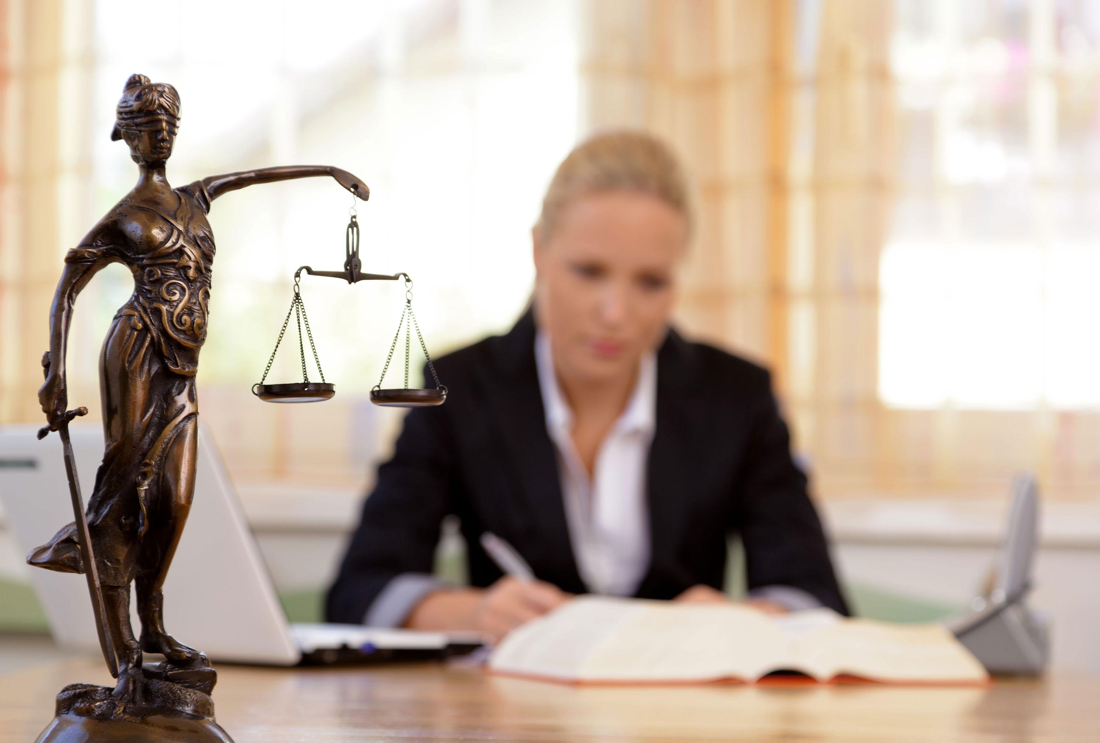 Anwältin am Schreibtisch mit Justitia-Statue im Vordergrund
